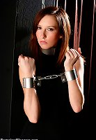 Sexy tight body girl in black dress gets her arms and legs shackled